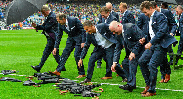 Members of the Cork 1990 Jubilee Football team race to collect their umbrellas after sitting for a team photograph yesterday.