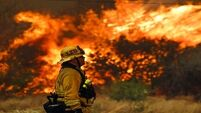 New fires re-erupt in California as heatwave blisters region