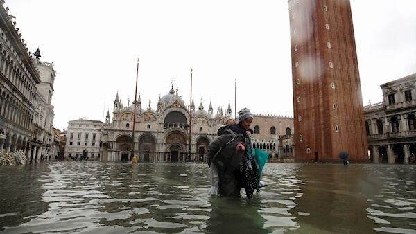 A woman carries her daughter in a flooded St. Mark's Square, in Venice, Italy, Tuesday, Nov. 12, 2019. (AP Photo/Luca Bruno)