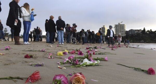 Family and friends gather on Sydney's Freshwater Beach following a candlelight vigil, where they threw hundreds of pink flowers into the ocean for Justine Damond who was shot by a Minneapolis last weekend.