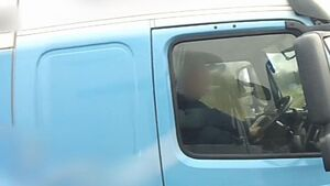 Police film lorry driver checking phone while resting foot on the dashboard