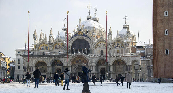 People walk in a snow-coated St. Mark's Square, in Venice, northern Italy. Pic: Riccardo Gregolin/ANSA via AP