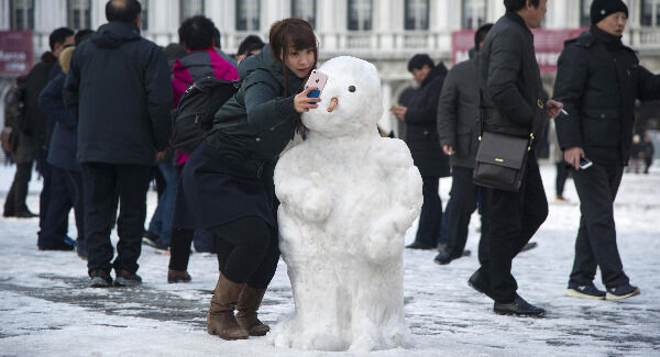 A tourist takes a selfie next to a snowman in St. Mark's Square, in Venice, northern Italy. Pic: Riccardo Gregolin/ANSA via AP