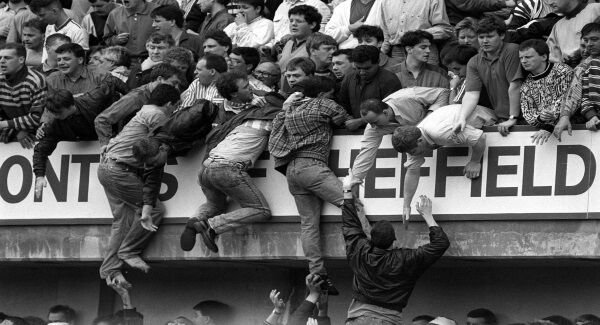 Liverpool supporters climb to safety during the FA Cup semi-final at Hillsborough in 1989. Picture: David Giles/PA Wire