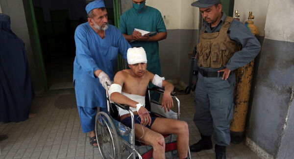 An injured man is moved by wheelchair at a hospital following a suicide attack in front of Kabul University. AP Photo/Rahmat Gul