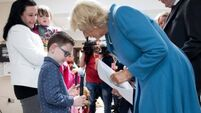 Boy gives Camilla a card in braille during Cork visit