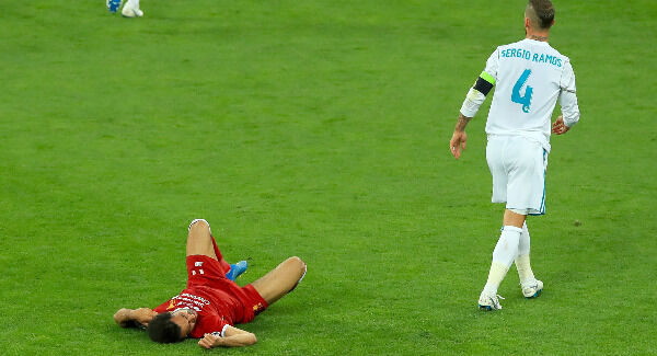 Mohamed Salah (left) lies injured on the pitch after a challenge from Sergio Ramos. Picture: Peter Byrne/PA Wire