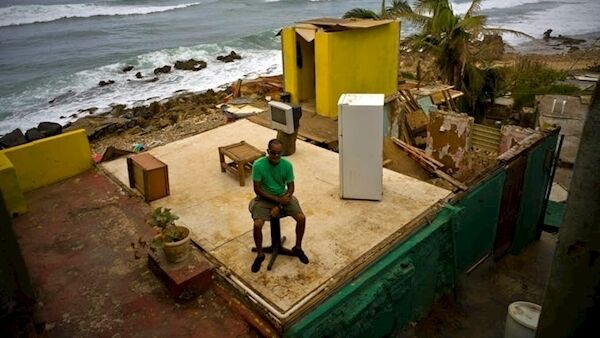 In this photo from October 2017, Roberto Figueroa Caballero sits in the ruins of his home after Hurricane Maria. (AP Photo/Ramon Espinosa, File)