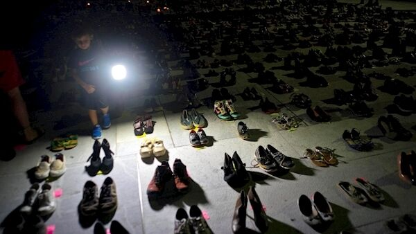 A child shines a light on hundreds of shoes at a memorial for those killed by Hurricane Maria, in front of the Puerto Rico Capitol in San Juan.(AP Photo/Ramon Espinosa, File)