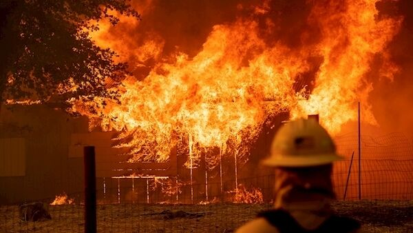 A firefighter monitors a burning outbuilding to ensure flames don't spread as the River Fire burns in Lakeport, California, last July. The US state was devastated by wildfires throughout 2018 Picture: Noah Berger/AP