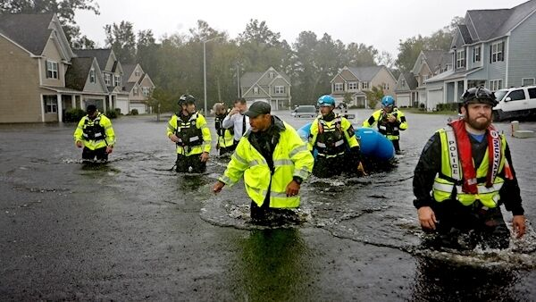 Members of the North Carolina Task Force urban search and rescue team wade through flood waters looking for residents who stayed behind as Hurricane Florence hit the US in September. Picture: David Goldman/AP