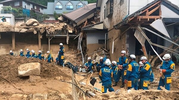 Emergency teams rest outside of structural damage caused by heavy rains last July in Hiroshima, Japan. Heavy rains caused extensive damage through flooding and mudslides. Picture: Haruka Nuga/AP