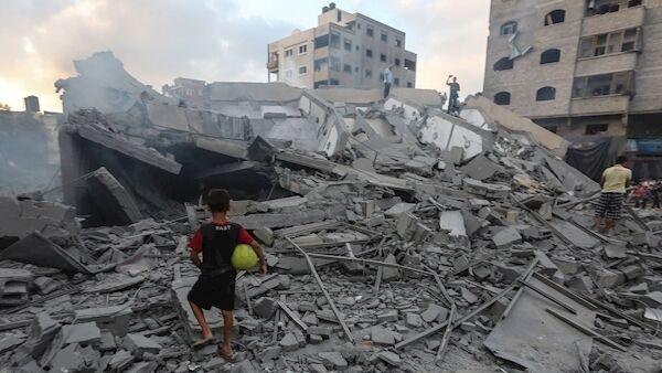 A boy stands by the rubble of the Al Mishal Culture Centre, destroyed by Israeli bombs.