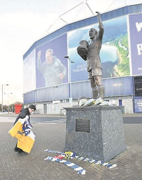 A young fan places a flag for missing player Emiliano Sala at the statue of Cardiff City legend Frederick Charles Keenor outside the stadium yesterday.