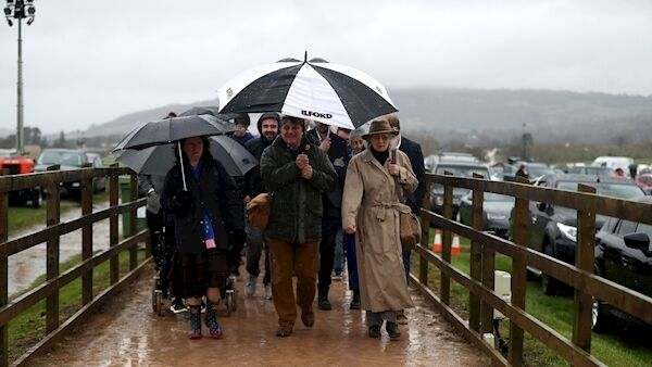 Racegoers carrying umbrellas arrive for Champion Day of the 2019 Cheltenham Festival at Cheltenham Racecourse. Picture: Simon Cooper/PA Wire