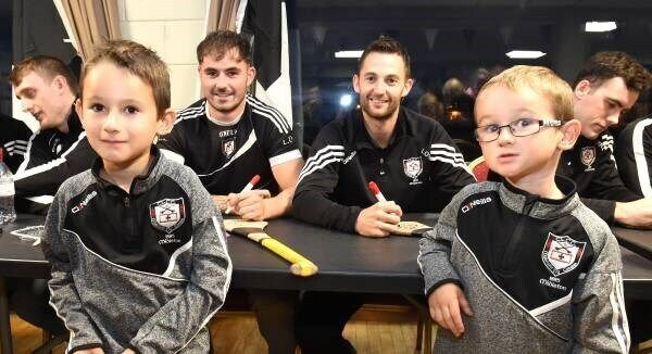 Young supporters Josh and Kalvin O'Brien pose for a picture with Luke Dineen and team captain Luke O'Farrell at the Midleton open night to meet the players. Picture: Larry Cummins
