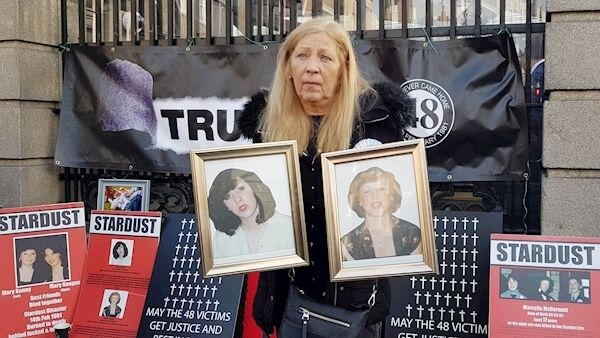 Antoinette Keegan outside the Dáil on the anniversary of the Stardust fire last February, holding pictures of her sisters, Martina and Mary, who died in the fire.