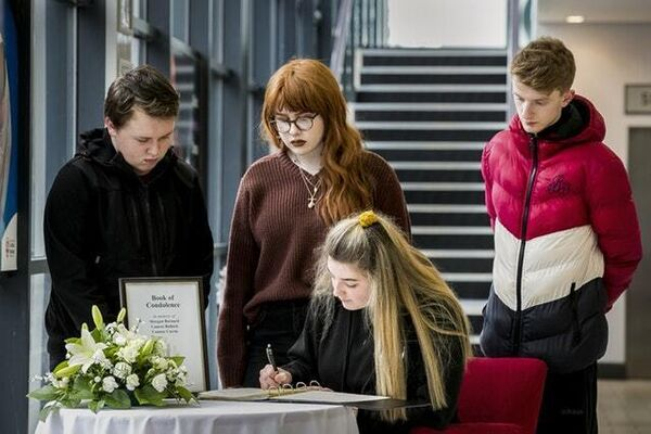 Youngsters sign a book of condolence in Cookstown (/PA)