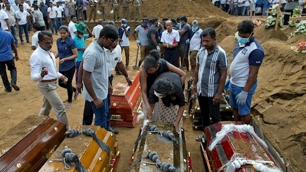 Anusha Kumari, center bottom, with bandages on her left eye touches coffins during a mass burial for her husband, two children and three siblings, all victims of Easter Sunday bomb blast in Negombo, Sri Lanka, Wednesday, April 24, 2019. (AP Photo/Gemunu Amarasinghe)