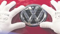 VW shares climb despite €1bn charge