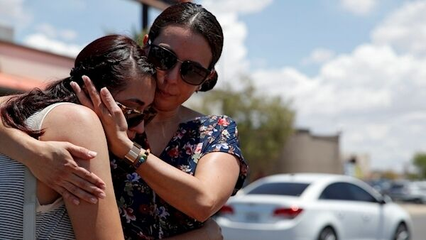 Cynthia Chavez, right, embraces her daughter Mia Chavez as they visit a makeshift memorial at the scene of a mass shooting at a shopping complex Sunday, Aug. 4, 2019, in El Paso, Texas. Picture: AP Photo/John Locher