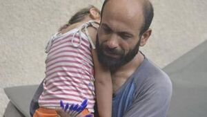 Thousands raised for refugee pictured selling pens while holding sleeping daughter
