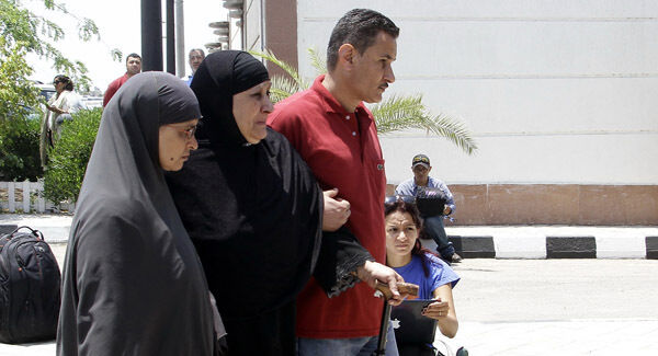 Relatives of passengers on an EgyptAir flight that crashed early Thursday walk past journalists at Cairo International Airport, Egypt yesterday. Picture: AP