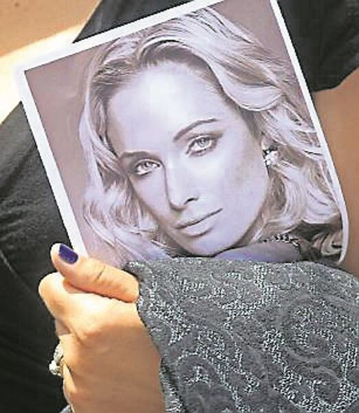 A mourner with a portrait of Reeva Steenkamp.