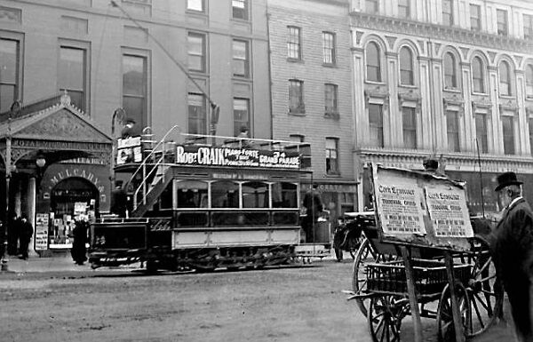 A tram is stopped outside the Victoria Hotel as agentleman keeps up to date on Boer War with the 'Cork Examiner'.