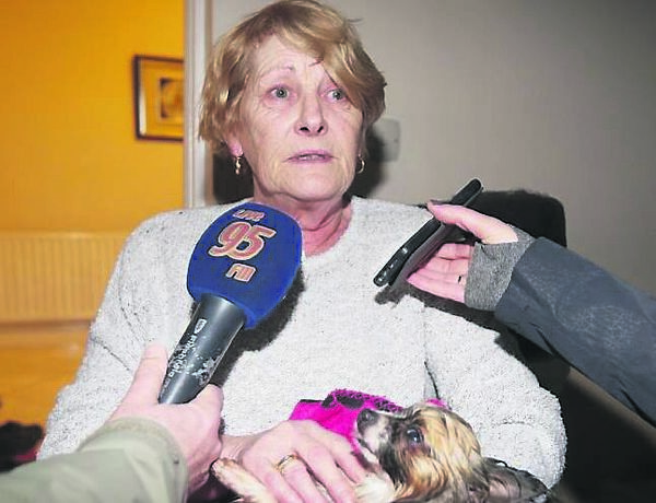 Vera O'Donnell holds her four-year-old dog Princess, who drowned when her home was flooded by canal water.