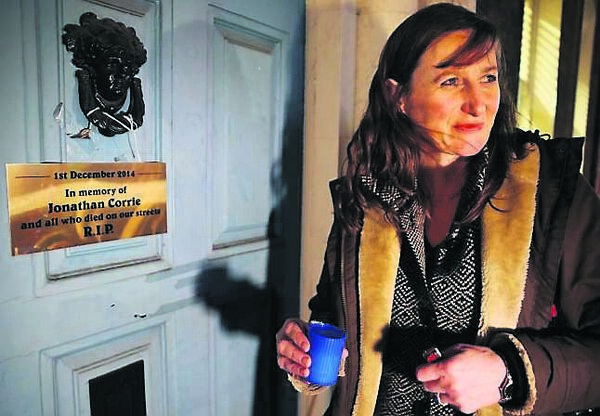 Director of Uplift Siobhán O'Donoghue lights a candle at the door where Jonathan Corrie died a year ago. Picture: PA