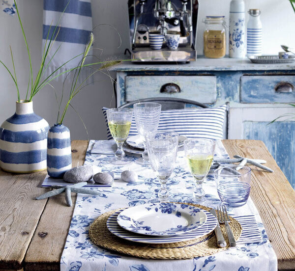 Blue and white are perfect for summer with the addition of rattan placemats to bring texture to this look which includes the Amanda latte cup €14, Sally water glass Ä10, Amanda table runner €15.90; sideplate €15, and Sally dinner plate £27.00, all by Danish brand Greengate at The Pavilion Garden Centre.