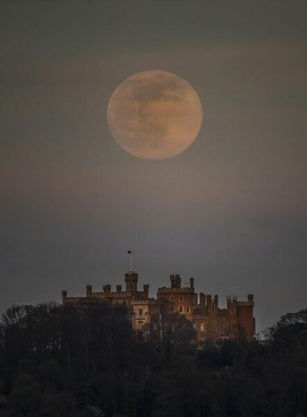 A pink supermoon is seen over Belvoir castle in Leicestershire (Danny Lawson/PA)