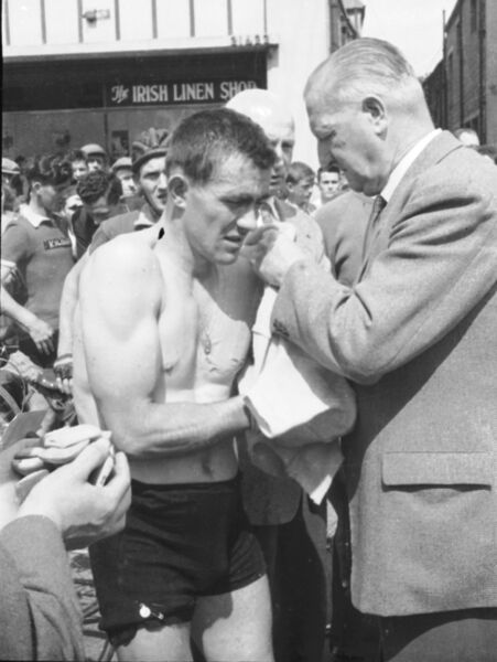 Mick Murphy having difficulty in putting on the Yellow Jersey in Tralee at the beginning of stage 4. His upper-body strength, somewhat unusual for a cyclist, is clearly evident. His legs were comparatively small. His holy medal is temporarily pinned to his torn shorts. The Jersey is being presented by Dr Eamon O'Sullivan who came from an old republican and sporting family – he was trainer of the Kerry Gaelic football team and was head of the NACA in Kerry. As such, he typified the nationalist-based sporting and political network that sustained the Rás in its early years.