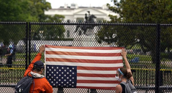 Demonstrators hold an American flag upside-down in protest near the White House in Washington yesterday.	Picture: Evan Vucci/AP
