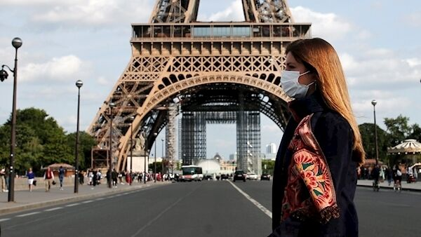 A woman wearing a facemask walks near the Eiffel Tower in Paris.