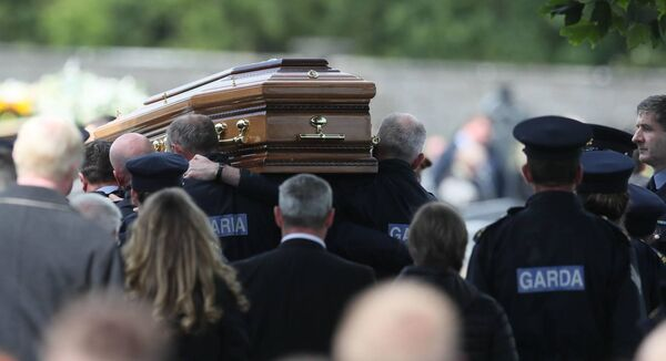 The coffin of Detective Garda Colm Horkan is carried from St James' church into the cemetery in Charlestown, Co Mayo. Picture: Brian Lawless/PA Wire