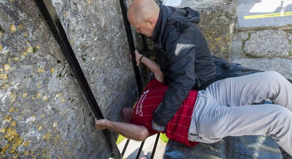 Dave Drohan holding Charles Colthurst as he kissed the Blarney Stone. Picture: Dan Linehan