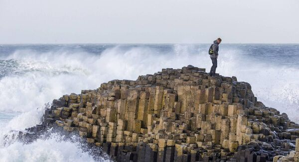 A tourist explores the Giant's Causeway. Heritage sites such as Giant's Causeway have also reopened. Picture: PA