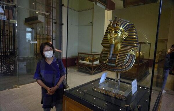 A Japanese tourist visits the golden mask of King Tut on display at the Egyptian Museum in Cairo (Hamada Elrasam/AP)