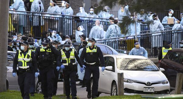Police officers and healthcare workers are stationed outside a public housing tower that is locked down as a Coronavirus hotspot in Melbourne, Australia, Wednesday, July 8, 2020. Picture: James Ross/AAP Image via AP