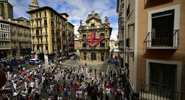 Residents, wearing white clothes and traditional red scarves, take to the streets on the day the ''txupinazo'' would usually take place to start the famous San Fermin festival, which was due canceled this year by the conoravirus, in Pamplona, northern Spain, Monday, July 6, 2020. Picture: AP Photo/Alvaro Barrientos