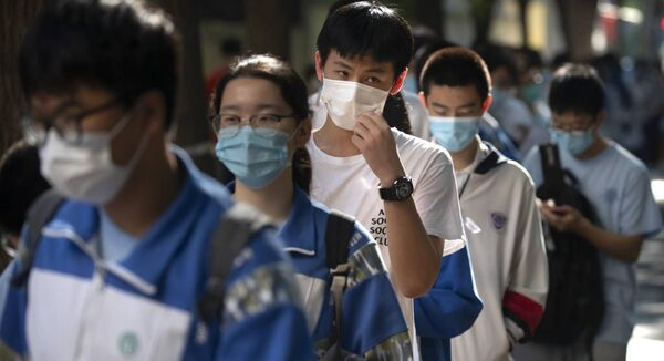 Students wearing face masks to protect against the new coronavirus line up for the first day of China's national college entrance examinations, known as the gaokao, in Beijing, Tuesday, July 7, 2020. Picture: AP Photo/Mark Schiefelbein