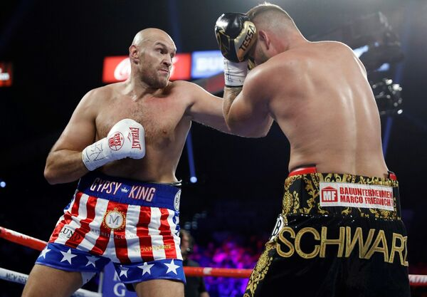 Tyson Fury, left, of England, tries to hit Tom Schwarz, of Germany, with a left during a heavyweight boxing match Saturday, June 15, 2019, in Las Vegas.