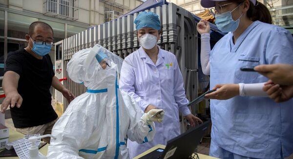 A worker wearing a protective suit talks with people registering for coronavirus tests at a community health clinic in Beijing. Picture: Mark Schiefelbein