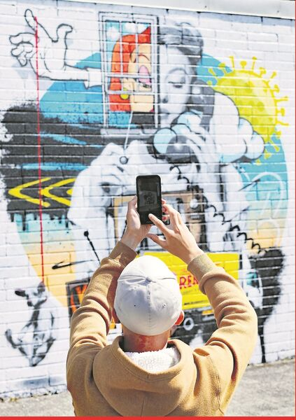 A man photographs a street art mural by the artist ADW in Portarlington, Co Laois. Entitled 'Is it Still raining? I hadn't noticed', the work deals with the issue of mental health during the Covid-19 lockdown. Picture: PA.