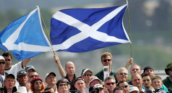 Spectators watch golfer Colin Montgomerie at the 2005 Open Championship with Scotland flags. File photo