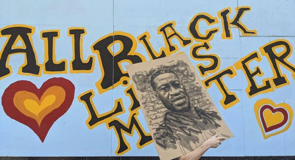 "A demonstrator carries an image of George Floyd in front of a boarded up business decorated with a mural reading ""All Black Lives Matter,"" on Hollywood Boulevard, during a march organized by black members of the LGBTQ community in the Hollywood section of Los Angeles, Sunday, June 14, 2020. (AP Photo/Damian Dovarganes)"