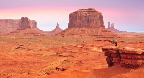Man on a horse, view from John Ford's Point in Monument Valley with the West Mitten Butte and the Merrick Butte in Utah-Arizona border, United States of America.