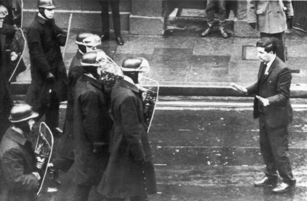 As a squad of helmeted riot police with shields move in to break up a mob of demonstrators, John Hume steps into their path pleading with them not to use violence in the centre of Derry on April 21, 1969.